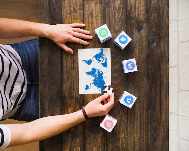 Man solving world map jigsaw puzzle near blocks of social networking icons Free Photo