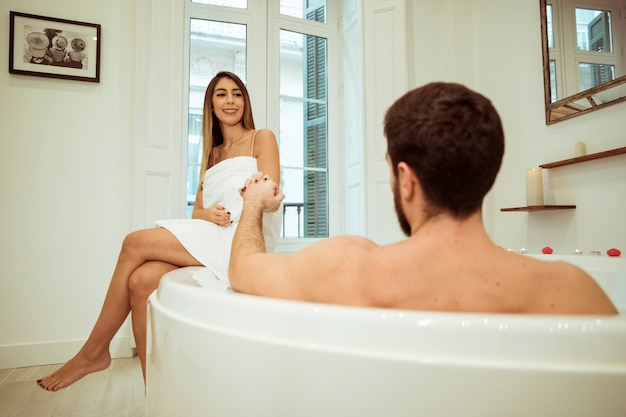 Man in spa tub holding hand of smiling woman Free Photo