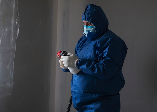 A man in a special suit paints walls with a spray gun, painting walls and ceilings Premium Photo