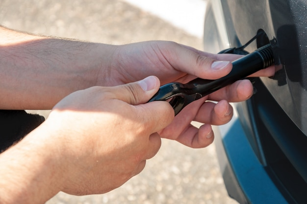 A man spins a hook for towing in front of a car. car breakdown and towing. Premium Photo