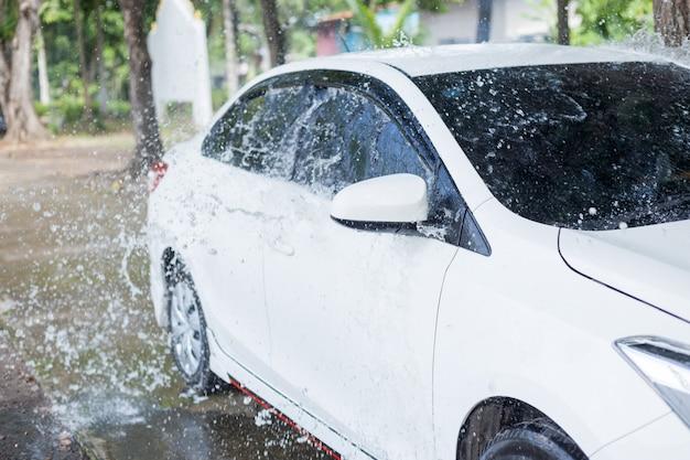 Man splashing water to white car for washing Premium Photo