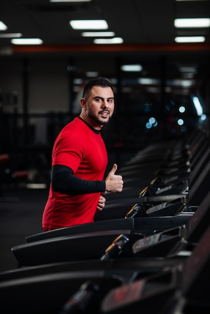 Man in sportswear running on treadmill at gym in red clothes Premium Photo