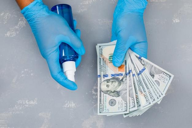 Человек, распыляющий дезинфицирующее средство на банкноты. Бесплатные Фотографии