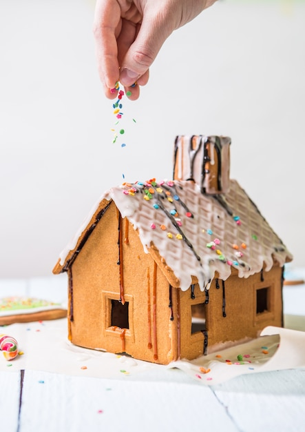 Man sprinkles homemade gingerbread house confectionery sprinkling Premium Photo