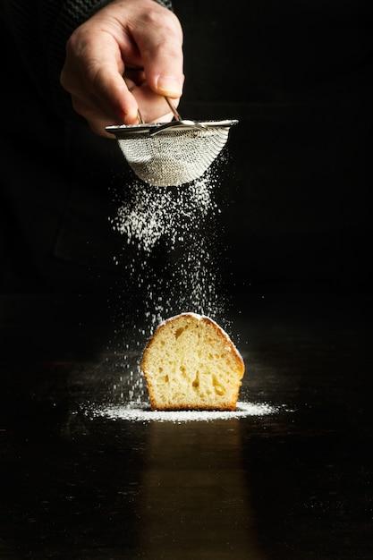 Человек посыпает сахарной пудрой кекс на темном фоне Premium Фотографии