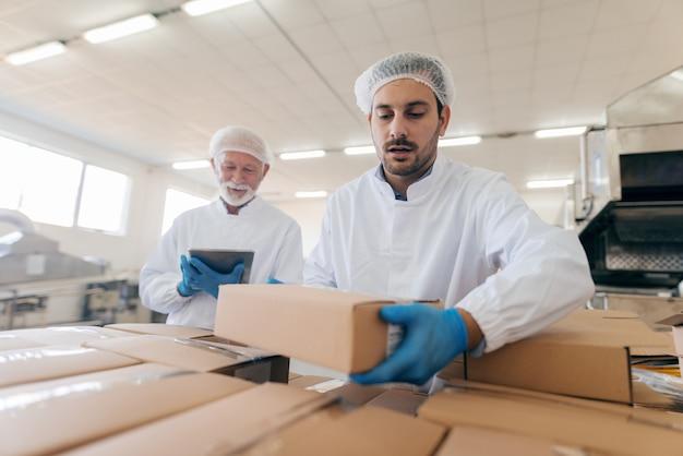 他の男が立ってタブレットを使用しながらボックスをスタッキングする男。食品工場のインテリア。 Premium写真