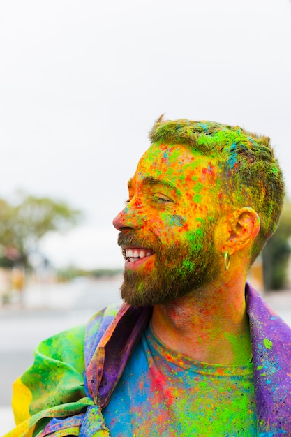Man stained paint powder with rainbow flag smiling on street Free Photo