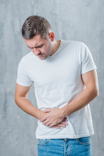 Man standing against gray background suffering from abdominal pain Free Photo