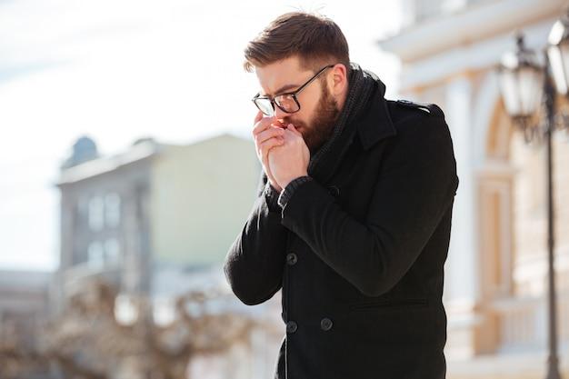 Человек стоит и кланяется на руках на улице в холодную погоду Бесплатные Фотографии