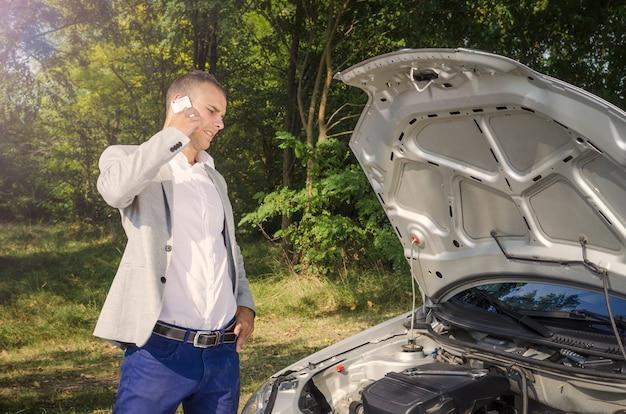 열린 후드 옆에 서서 전화를 걸고 차량을 고치려는 남자 무료 사진