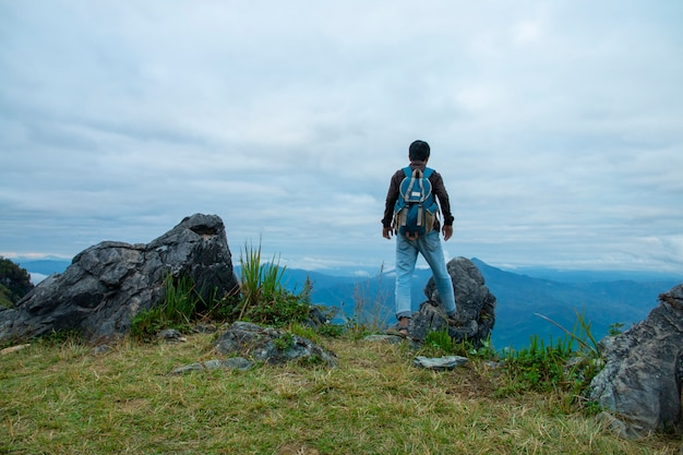 Man standing on the cliff and looking at the valley and mountains in the daylight Premium Photo