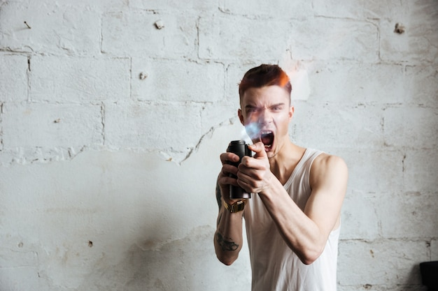 Uomo in piedi sul pavimento con gas spray Foto Gratuite