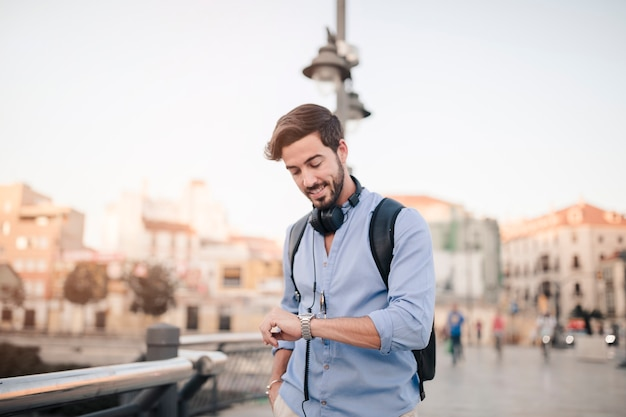 Man standing in front of city building looking at time on watch Free Photo
