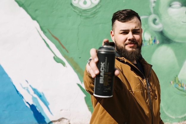 Man standing in front of graffiti wall with aerosol can in hand Free Photo