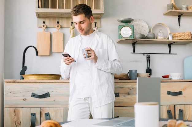 Man standing in front of kitchen counter using mobile phone holding coffee cup Free Photo