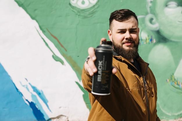 Человек, стоящий перед стенами граффити с аэрозолем, может в руке Бесплатные Фотографии