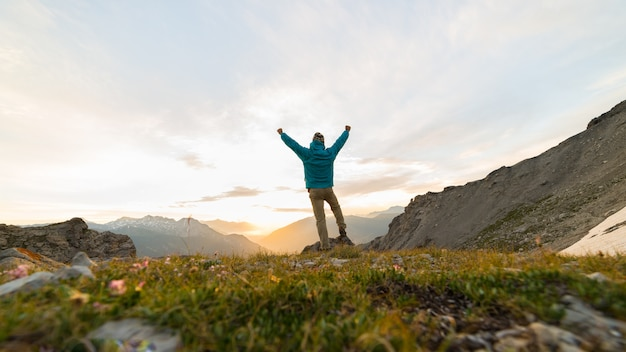 Man standing on mountain top outstretching arms, sunrise light colorful sky scenis landscape. Premium Photo