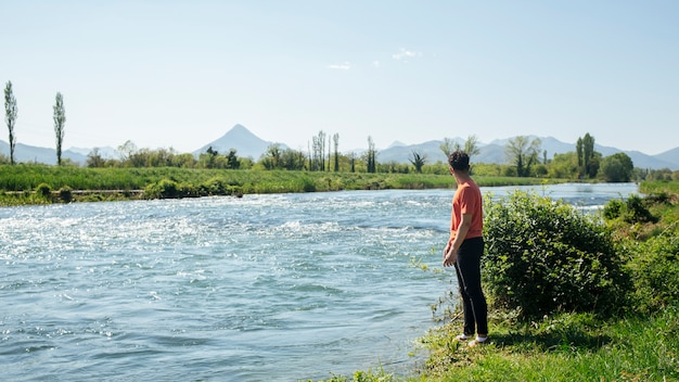 Man standing near natural flowing river Free Photo