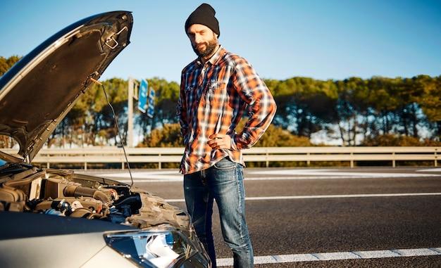 壊れた車の隣に立っている男性 無料写真