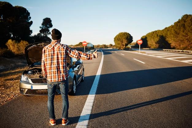 Человек, стоящий рядом со своей сломанной машиной Бесплатные Фотографии