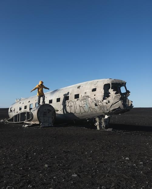 放棄された墜落した飛行機に立っている人 無料写真