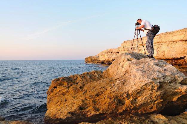 岩の上に立っていると黒海の三脚で写真を撮る男 Premium写真