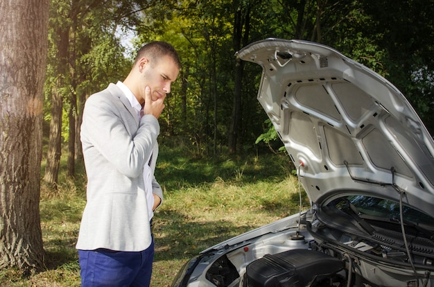 Uomo in piedi sulla strada vicino alla macchina rotta e pensando a come ripararlo Foto Gratuite