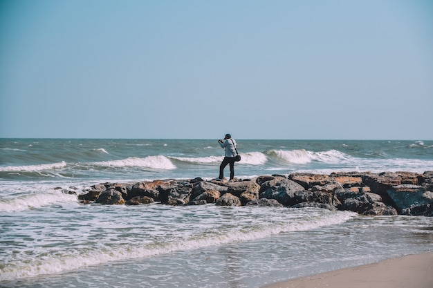 Man standing on rock view on beach and sea Premium Photo