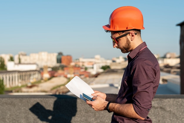 Man standing on rooftop with phone in hand Free Photo