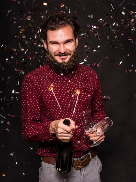 Man standing under spangles with glasses and sparklers Free Photo