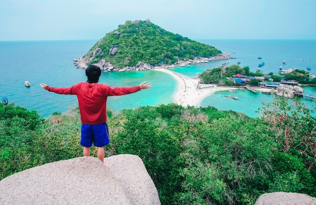 A man standing on top mountain and looking to island. Premium Photo
