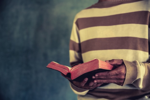 A man standing while reading bible or book over concrete wall with window light Free Photo