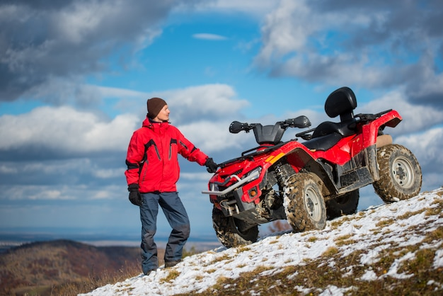 Man standing in winter clothes near atv on a snowy hill Premium Photo