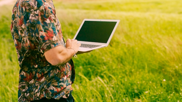 Man standing with laptop in glade Free Photo