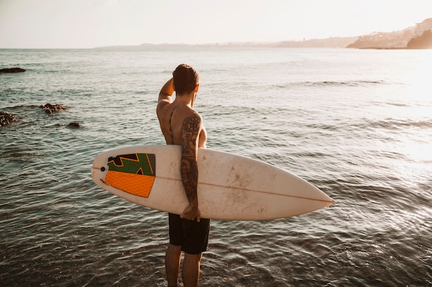 Man standing with surfboard in sea Free Photo