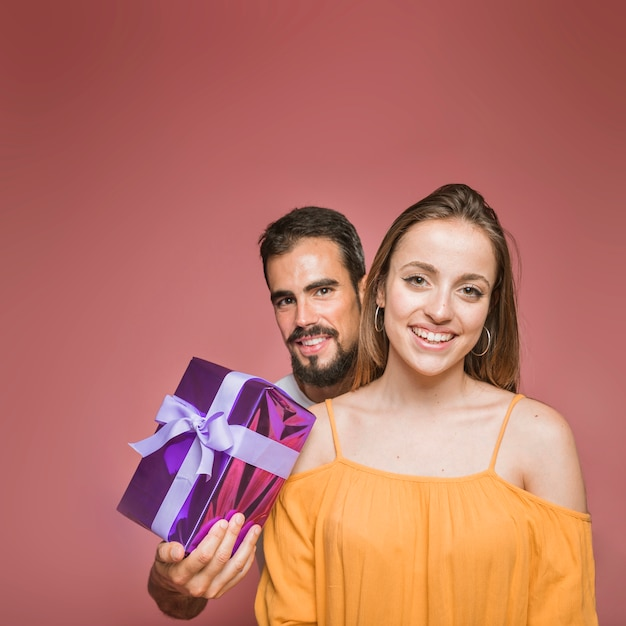 Man standing behind the woman holding present on colored background Free Photo