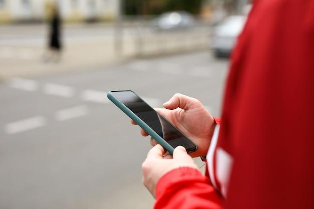 男は彼の手に電話で岐路に立っています。 Premium写真