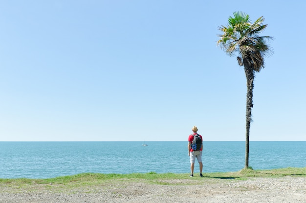 Man stands near of a tall palm tree on a background of sea and blue sky Premium Photo