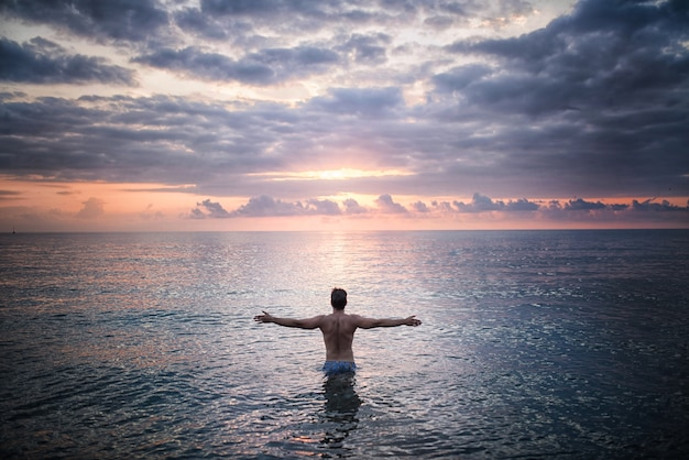 Man stands in the sea water facing sunset Free Photo