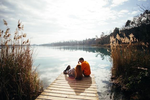 L'uomo si trova sulla riva del lago di garda contro il cielo al tramonto Foto Gratuite