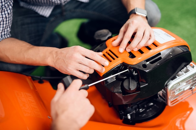 A man starts a lawnmower motor in the store. Premium Photo