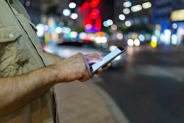 Man on the street with phone in hands Premium Photo