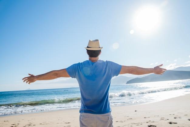 Человек, растяжения оружия на пляже Бесплатные Фотографии