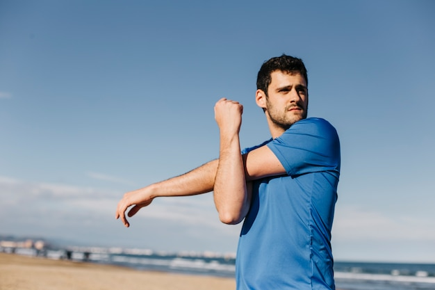 Man stretching at the beach Free Photo