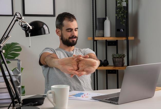 Uomo che allunga le braccia mentre si lavora da casa Foto Gratuite