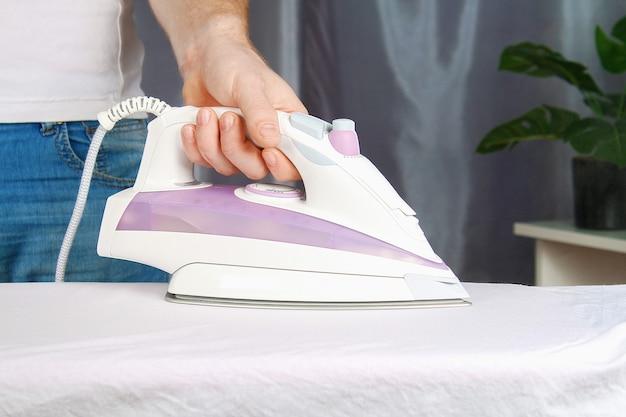 男はアイロン台に黒い電気アイロンでリネンを撫でます。 Premium写真