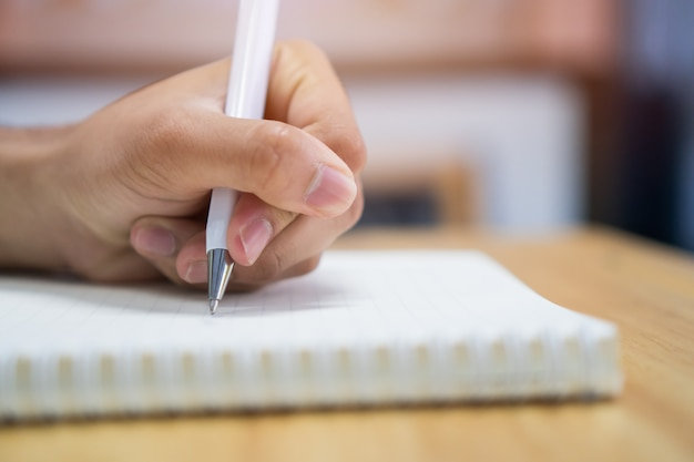 Man student taking and writing notes on notebook in college university for homework Premium Photo