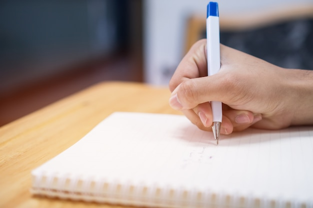 Man student taking and writing notes on notebook with pen in library at college university Premium Photo