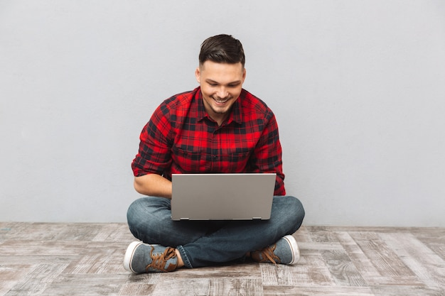 Man student working on laptop while sitting on the floor Free Photo