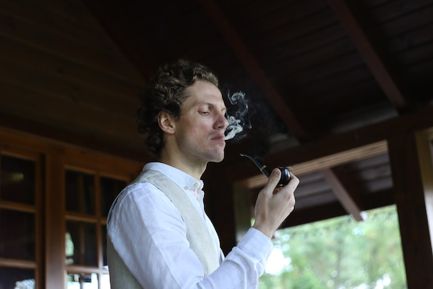 Man in stylish clothes smoking a pipe releasing smoke outside the residence Free Photo